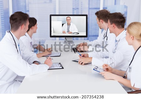 Team of doctors having video conference meeting in hospital - stock photo