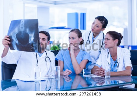 Team of doctors looking at xray in the meeting room - stock photo