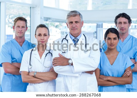 Team of doctors standing arms crossed in the hospital - stock photo