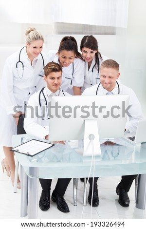 Team of doctors using desktop PC together at desk in clinic - stock photo