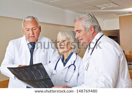 Team of doctors watching x-ray image in a hospital - stock photo