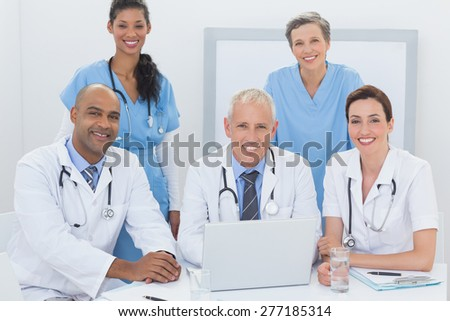 Team of doctors working on laptop in medical office