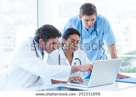 Team of doctors working on laptop in medical office - stock photo