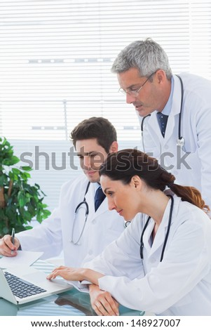 Team of doctors working together and watching something on their laptop in medical office