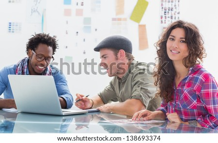 Team of editors at work with one smiling at camera in modern creative office - stock photo