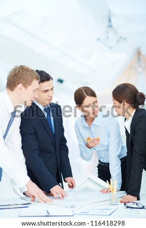 Team of engineers discussing blueprint at meeting - stock photo