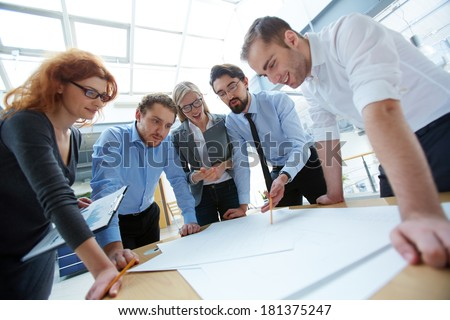 Team of engineers discussing blueprint at meeting