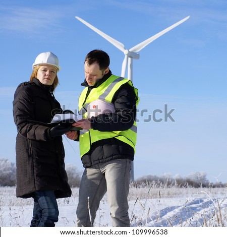 team of  engineers or architects with white safety hat and wind turbines on background