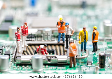 Team of engineers repairing circuit board. Computer repair concept - stock photo