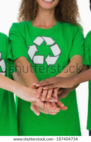 Team of environmental activists putting hands together on white background - stock photo