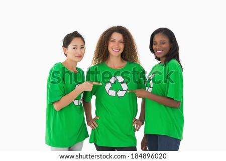 Team of environmental activists smiling at camera pointing to tshirt on white background - stock photo
