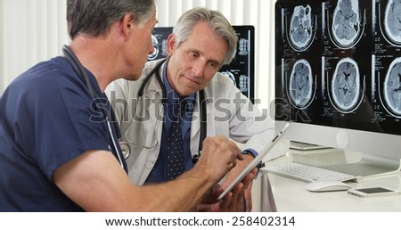Team of experienced senior doctors working in the office - stock photo