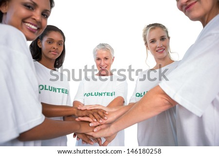 Team of female volunteers with hands together smiling at camera on white background - stock photo