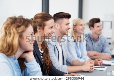 Team of Five Smiling Young Office Workers Sitting at the Boardroom Table, Looking to the Right of the Frame While Listening to Someone.