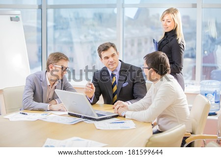 team of four business people discussing an important question at briefing - stock photo