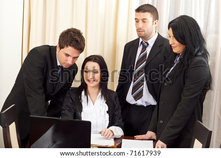 Team of four business people having a meeting  working on laptop and having conversation - stock photo