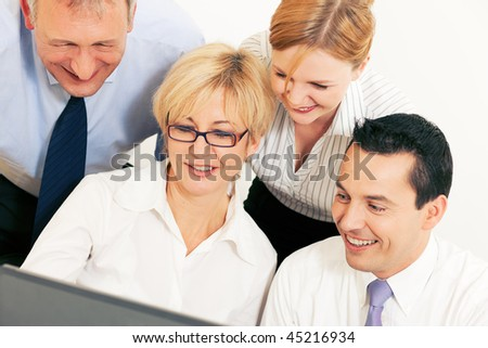 Team of four business people working in front a computer looking at the screen, seeing something good obviously - stock photo