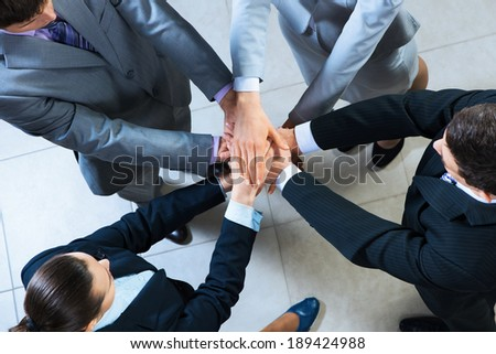 team of four businessmen with folded hands, a symbol of teamwork - stock photo