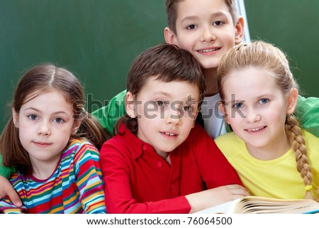 Team of four classmates looking at camera in classroom - stock photo