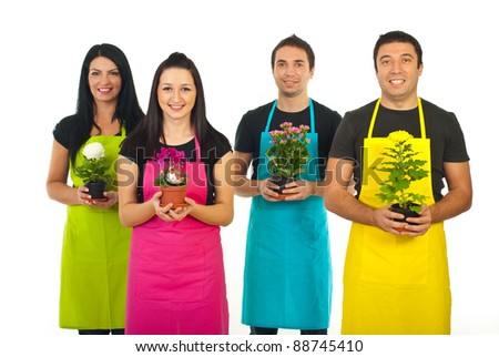 Team of four gardeners workers in colorful aprons offering flowers pots isolated on white background