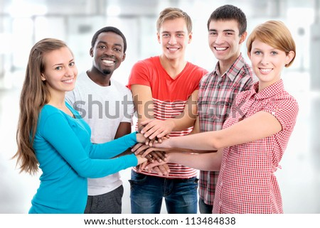 Team of friends showing unity with their hands together - stock photo