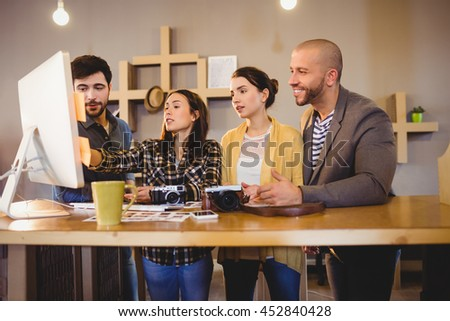 Team of graphic designers working on a computer in office