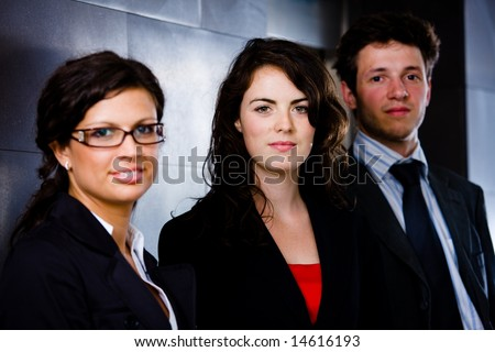 Team of happy business people standing at office corridor, looking at camera, smiling. Dark background.