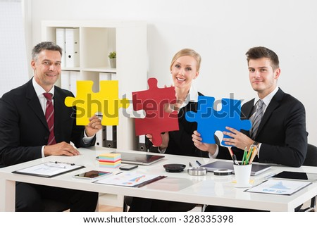Team Of Happy Businesspeople Holding Multi-colored Jigsaw Puzzle In Office - stock photo