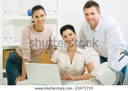Team of happy office people working on laptop computer.