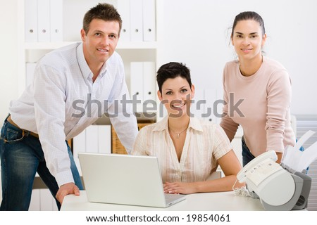 Team of happy office people working on laptop computer, smiling. - stock photo