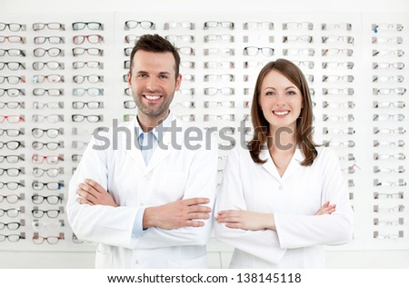 Team of happy opticians optometrists standing in optical shop - stock photo