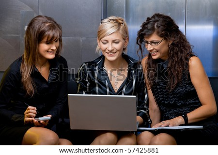 Team of happy young businesswoman having a meeting, using laptop computer, smiling. - stock photo