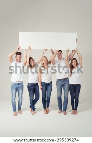 Team of Happy Young People in Casual White Shirts and Blue Jeans, Holding an Empty Rectangular Board with Copy Space Up. Captured in Studio with Off-White Background. - stock photo