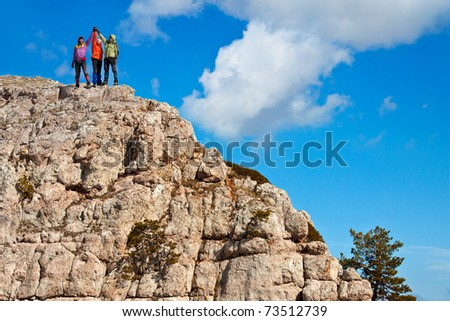 Team of hikers on the rocky summit - stock photo