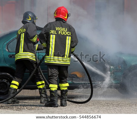team of Italian fire brigade extinguished the car fire after the car accident with the words in the jacket that means FIREMEN in Italian language