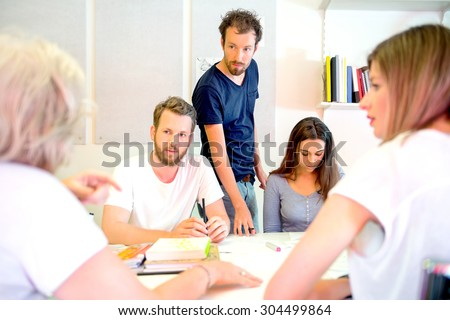 Team of male and female 3D designers discussing at desk in printing studio - stock photo