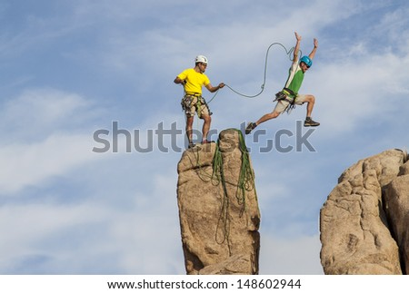 Team of male climbers conquer the summit of a challenging rock spire. - stock photo
