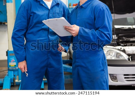 Team of mechanics talking together at the repair garage - stock photo