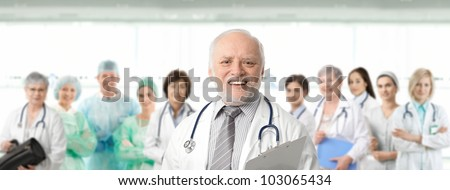 Team of medical professionals lead by senior white haired doctor looking at camera, smiling. - stock photo
