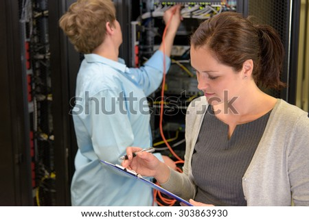 Team of network technician in datacenter checking security on servers - stock photo