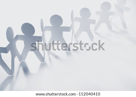 Team of paper doll people holding hands. - stock photo