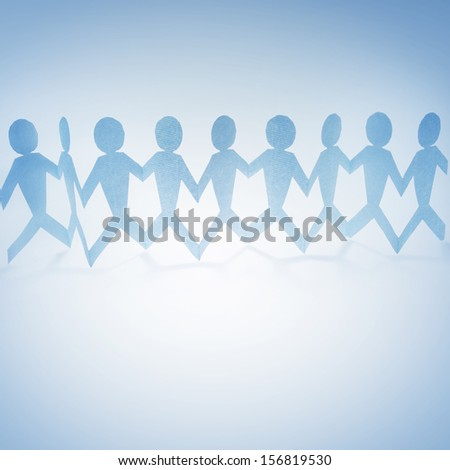 Team of paper doll people holding hands on blue tone background