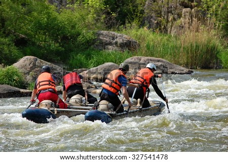 Team of people on an inflatable catamaran row up the stream in a thresholds. Southern Bug river, Ukraine. - stock photo