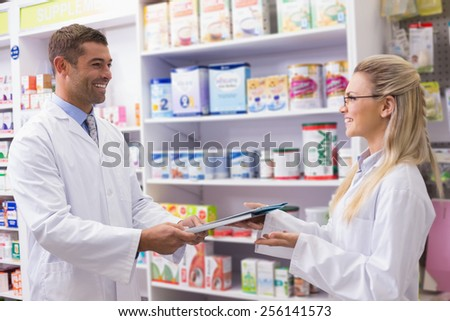 Team of pharmacists holding clipboard smiling at camera at the hospital pharmacy