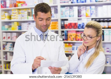 Team of pharmacists holding paper and talking at the hospital pharmacy