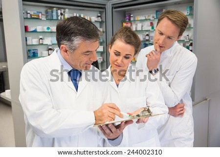Team of pharmacists looking at clipboard at the hospital pharmacy - stock photo