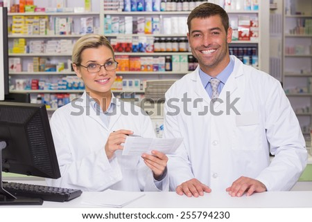 Team of pharmacists looking at paper at the hospital pharmacy