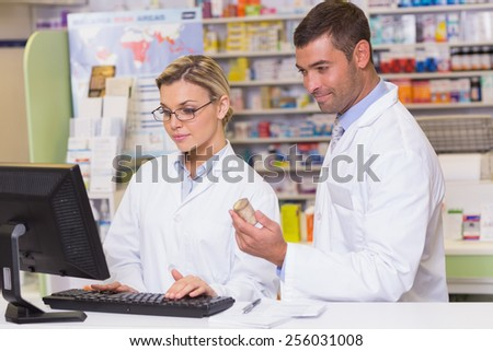 Team of pharmacists looking at the computer at the hospital pharmacy