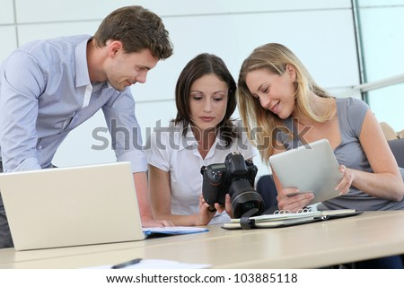 Team of photo reporters working in office - stock photo