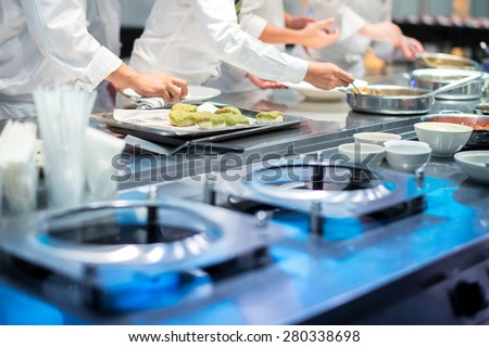 Team of restaurant chef helping each other to finish the good food for customer in five star hotel - stock photo